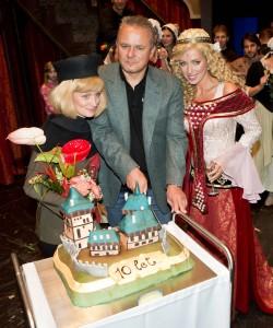 Egon Kulhánek rozkrajuje dort k 10 letům Noci na Karlštejně